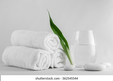 Spa setting decorated with green leave towel  and white stone.