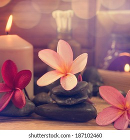 Spa setting with frangipani flower, essential oil, zen stones and aromatic candles on table, Zen concept in vintage retro style.