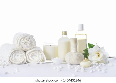 Spa setting with green leaves on rolled towel, bottle oil , herbal ball, gardenia ,salt in bowl candle ,pile of white stones