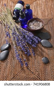 Spa setting with Lying on lavender with black stones, ,bottle oil,salt in bowl