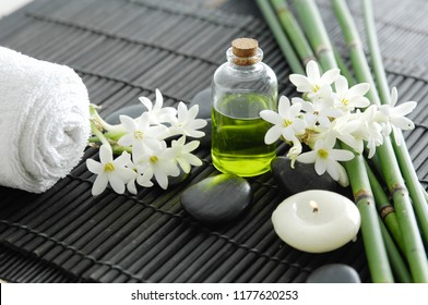Spa setting on mat with black stones, candle, lying on white flower, bamboo grove
