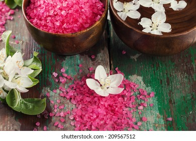 Spa setting on old wooden background. Water with aroma oil, sea salt, flowers. Selective focus, horizontal.