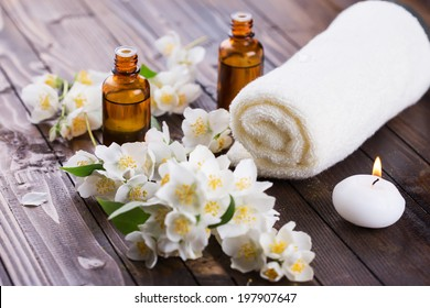 Spa setting on wooden background. Towel, aroma oil, candle, flowers. Selective focus, horizontal.