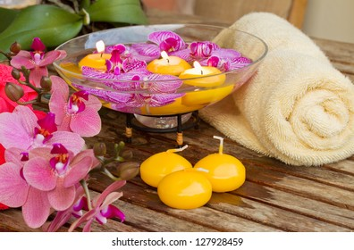 spa setting with orchid flowers and candles on wooden table