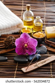 Spa setting with pink orchid, oil, soap on mat