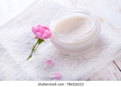 Spa setting with pot of moisturizing cream beautiful pink roses and rose oil on white background top view Flat lay