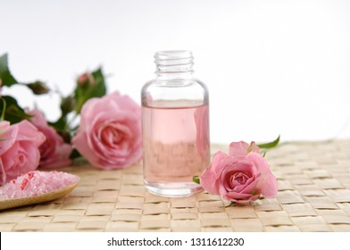 Spa setting with rose, salt in spoon, bottle oil on mat
