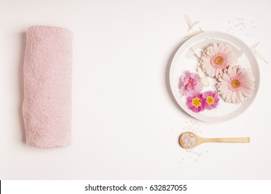 Spa setting. Sea salt, candles, floating flowers, towels on rustic  background