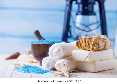 Spa setting with soap, towels, sea salt on  painted wooden boards. Selective focus is on towels.