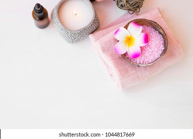 Spa setting top view with body products, body care wellness with plumeria flower, cotton towels, bath salt, flower, oil bottle and scented candle on wooden background, spa resort relaxing and skincare