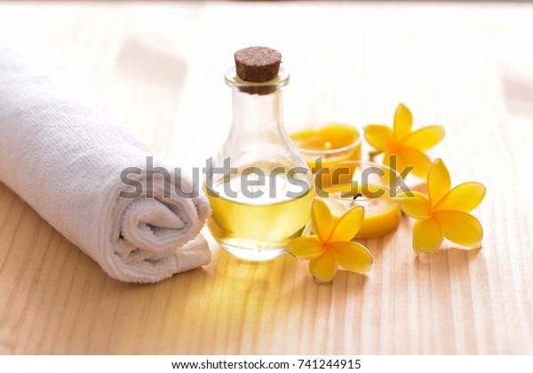 Spa setting with yellow candle, soap,yellow frangipani,bottle oil on wooden backgrounda