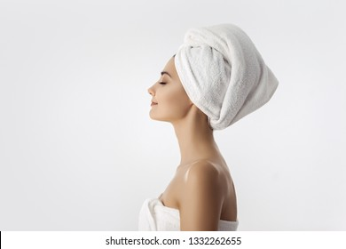 Spa skin care beauty woman wearing hair towel after beauty treatment. Beautiful multiracial young woman with perfect skin isolated on white background. Mixed race Caucasian Asian with closed eyes
