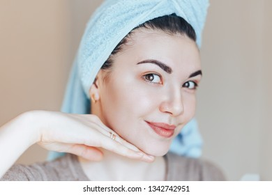 Spa skin care beauty woman wearing hair towel after beauty treatment. Beautiful young woman with perfect skin smiling looking at camera touch her face. close up selected focus