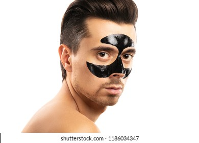 Spa and skin care for men. Young guy with a black charcoal mask on his face on white background.