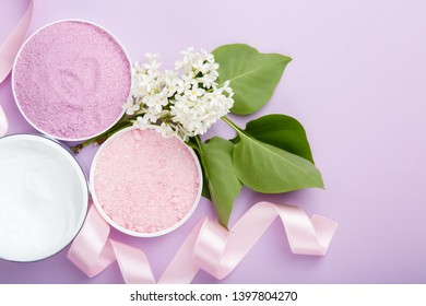 Spa and skin care products (cream, and sea bath salt) on purple background with spring white lilac blossom. Freshness natural anti-age relax care. Female spa cosmetics with heart from ribbon, love