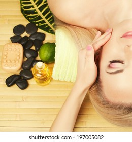 Spa and skincare concept. Portrait of beautiful girl receiving and enjoying face massage. Closed eyes. Perfect skin and make-up. Close up. Studio Shot
