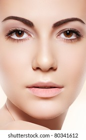 Spa, skincare, wellness & health. Front close-up portrait of beautiful female model face with purity health skin & light make-up on bright beige background