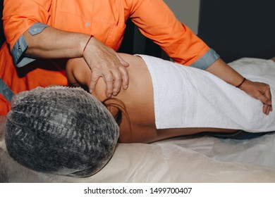 a spa specialist is twisting the spine of a young girl in a medical cap. bodily procedures close-up. recovery from back pain.