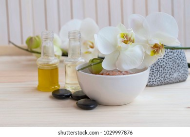 Spa still life with bath salt, white orchid flower and bath oils with massage stones
