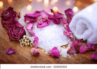 Spa still life with bath salt purple rose and a towel on a wooden table