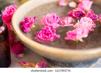 Spa still life with bowl of skincare treatment with roses and oil, selective focus