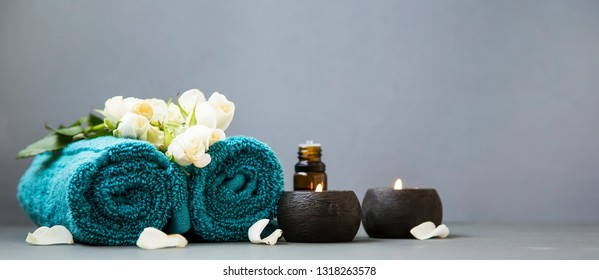 Spa still life with candles, towels and flowers on grey background copy space, spa and wellness still life
