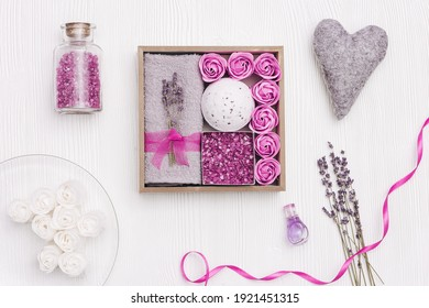 Spa still life composition with items for body care with lavender aroma on white wood surface. Personal gift box from sea salt, bath roses, bomb, towel, lilac dry flowers.