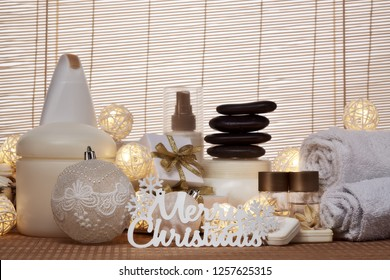 Spa still life with cosmetic creams,  towel, black stones, gift boxes and Christmas ornaments standing on bamboo mat. Christmas Healthy lifestyle, body care, Spa treatment and relaxation concept