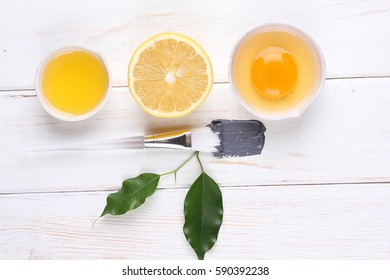 Spa still life with essential oil, clay mask, lemon, egg, face cream with brush on black and white wooden background
