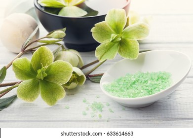 SPA still life, green bath salt, cosmetic products and lit candle on white wooden background