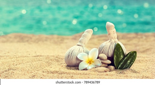 Spa still life with herbal balls and frangipani flowers for a massage and flower essence . Marine background , on the beach with warm sand and turquoise sea .