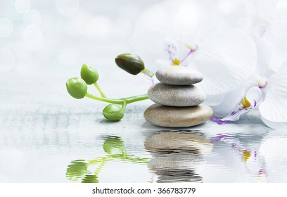 Spa still life with massage stones,white orchid on water reflection