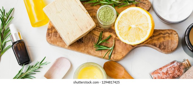 Spa still life with organic ingredients , top view of natural soap, clay, essential oil, rosemary herb, lemon and bath salt on wooden board, organic ingredient for skincare treatments and masks