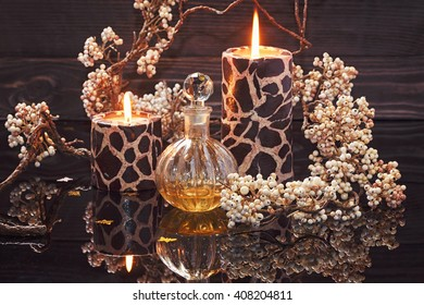 Spa still life with perfume and aromatic oils bottle surrounded by flowers and candles, on dark background