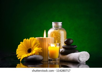Spa still life with sea salts, candles, yellow flower, white towel and stones on a green background