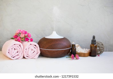 Spa still life setting with aromatherapy diffuser, towels, rose oil bottles and bath salt on concrete background