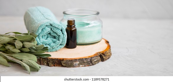 Spa still life setting with candle, sage oil bottle, sage leaves and cotton towel, wellness spa setting
