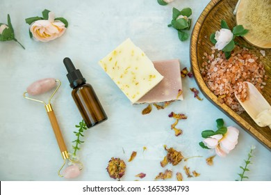 Spa still life setting with natural soap, rose quartz face roller, rose oil bottle and bath salt , top view