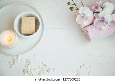 Spa still life setting with orchid flower, natural soap, towels and candle, spa and aromatherapy still life set on concrete background top view