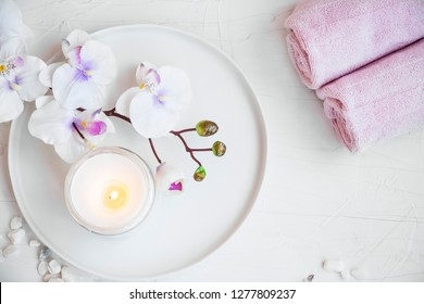 Spa still life setting with orchid flower, towels and candle, top view of spa still life set
