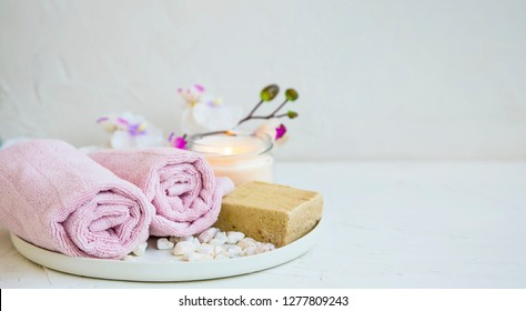 Spa still life setting with orchid flower, natural soap, towels and candle, spa and aromatherapy still life set on concrete background