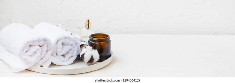 Spa still life setting with white cotton buds and towels, scented candle and perfume bottle, minimal interior still life and decor