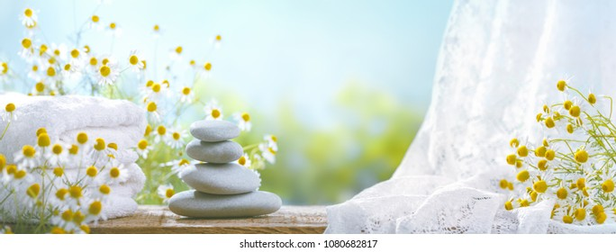 Spa still life with stack of stones,towel and chamomile flower.