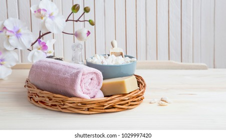Spa still life with towel, bath salt and natural soap in a tray with orchid flower, spa setting still life and wellness concept