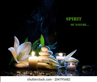 spa still life with white lily, stones and  burning candles on  black bright table with water drop,  on black background