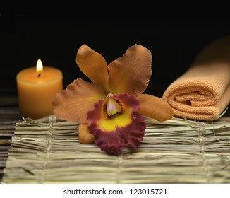 Spa still with orange orchid and candle with towel on mat