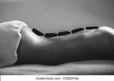 Spa Stone Massage. Beautiful Woman Getting Spa Hot Stones Massage in Spa Salon. black and white