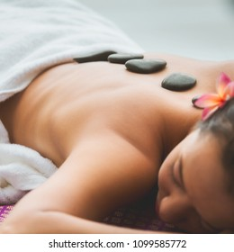 Spa Stone Massage concept, Close up of beautiful young asia woman Getting traditional spa hot stones massage in pool spa resort, Thailand