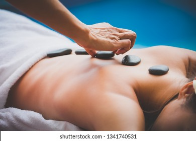 Spa Stone Massage concept, Close up of beautiful young asian woman Getting traditional spa hot stones massage in pool spa resort, Thailand