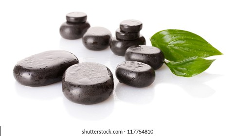 Spa stones with drops and green leaves isolated on white